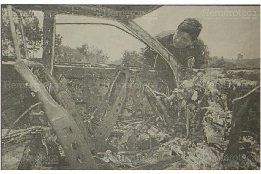 Un investigador  de la Policia Nacional busca en el  vehículo quemado alguna evidencia. ( Foto: Hemeroteca PL)