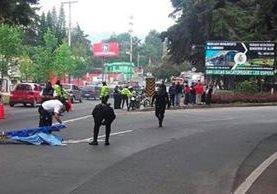 Socorristas resguardan el cadáver de una víctima del ataque armado registrado en un autobús en San Lucas Sacatepéquez. (Foto Prensa Libre: Érick Ávila)