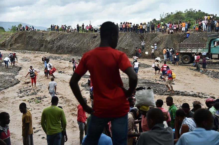 Personas tratan de ponerse a salvo al cruzar un río en Haití. (Foto Prensa Libre: AFP).