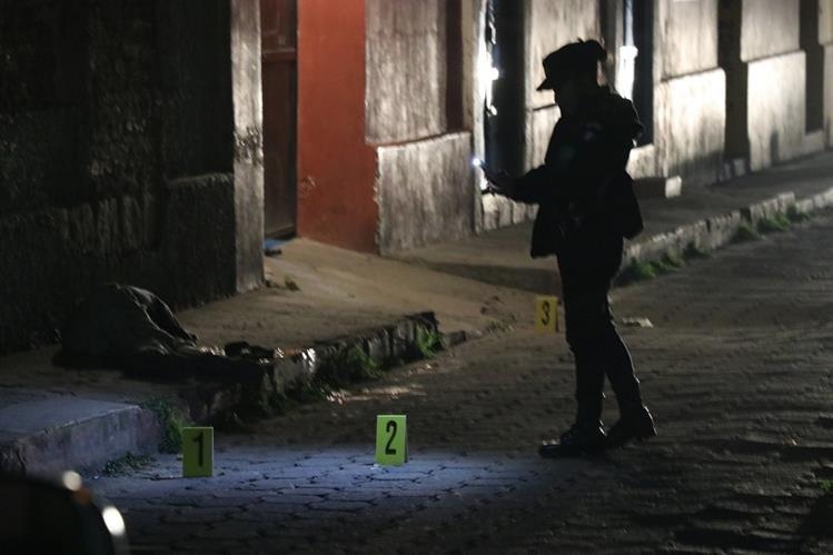 Investigadores del MP recolectaron indicios en la escena crimen, en la zona 1 de Xela, y toman fotografías del lugar y de la víctima. (Foto Prensa Libre: María José Longo)