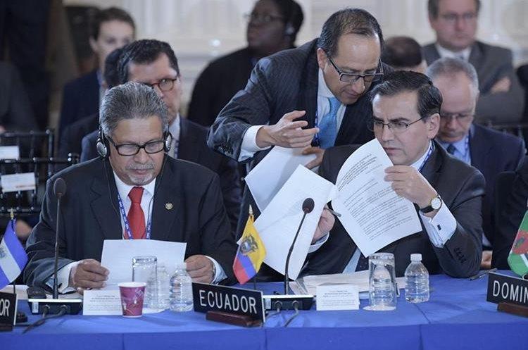 Los embajadores ante la OEA, Carlos Calles Catillo (i) de El Salvador, y José Valencia Amores (d) de Ecuador, leen unos documentos durante Asamblea. (EFE).