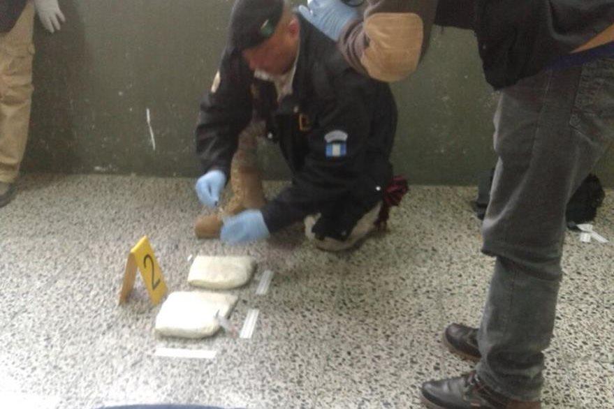 Autoridades examinan narcóticos localizados en un autobús, en San Antonio Sacatepéquez, San Marcos. (Foto Prensa Libre: PNC)