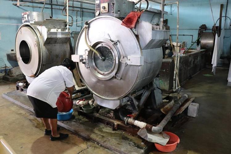 Personal del área de lavandería colocan recipientes, debido a que la lavadora también tiene fuga de agua. (Foto Prensa Libre: Cristian Icó)