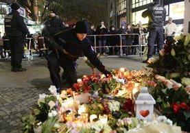 Un policía coloca flores y velas en memoria de las víctimas del atentado en Berlín. (Foto Prensa Libre: EFE).