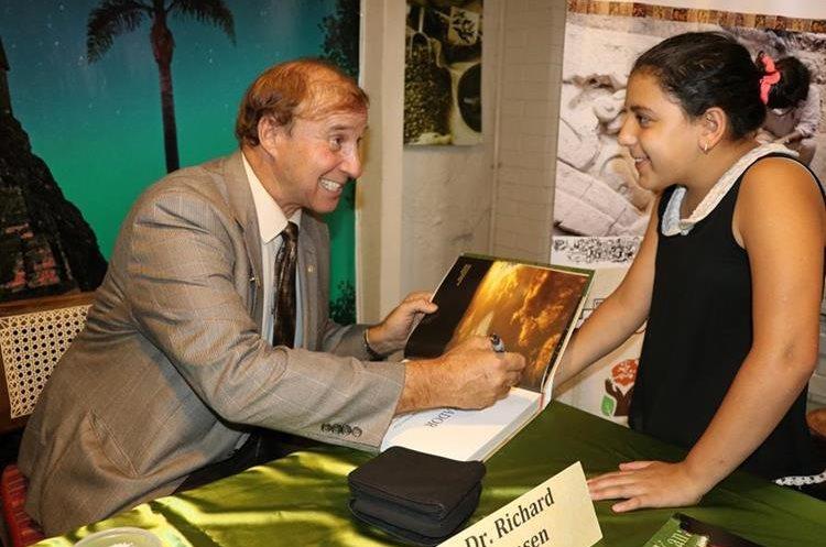 El arqueólogo Richard D. Hansen entrega el libro a una estudiante del colegio Colonial Bilingüe de Antigua Guatemala.(Foto Prensa Libre: Julio Sicán)