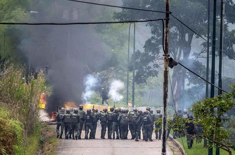 Miembros de la Guardia Nacional Bolivariana dispersan a un grupo de manifestantes en Caracas. (Foto Prensa Libre: EFE)