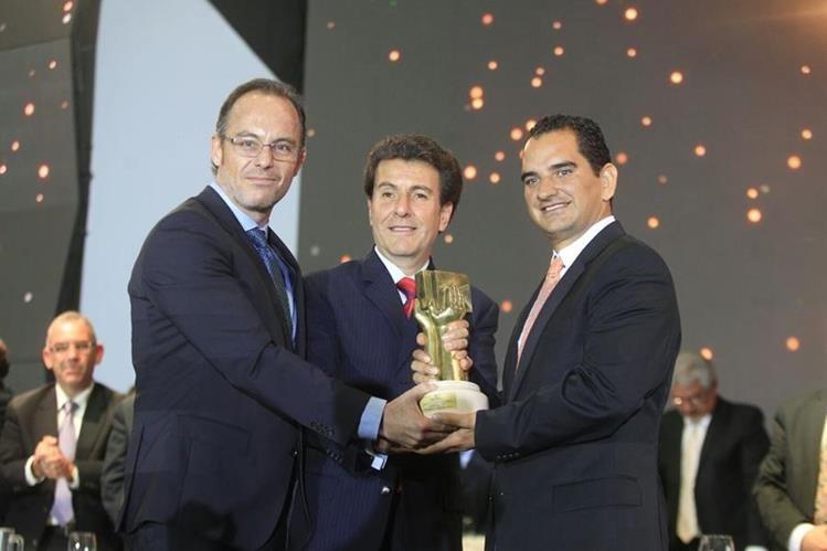Rolando Paiz, presidente de Agexport y Jorge Méndez, ministro de Economía, entregan el galardón a Alejandro Cruz, gerente de Jardínes Mil Flores.