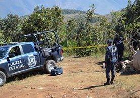 Policías de la Fuerza Estatal resguardan el sitio donde peritos forenses trabajan sobre el hallazgo de las fosas clandestinas, en Zitlala, Guerrero. (Foto Prensa Libre: EFE).