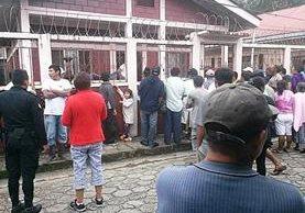Pobladores de Lívingston, Izabal, observan el interior de vivienda donde se halla cadáver de septuagenario ultimado por su hijo. (Foto Prensa Libre: Dony Stewart)