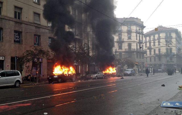 Dos vehículos arden en Milán, ciudad italiana que ha vivido una jornada de violentas manifestaciones. (Foto Prensa Libre: EFE).