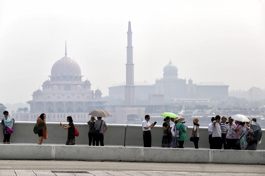Una neblina gris envuelve el edificio en el que se encuentran oficinas oficiales en Putrajaya, Malasia.  La ciudad suele experimentar días de extrema contaminación. (Foto Prensa Libre: EFE).