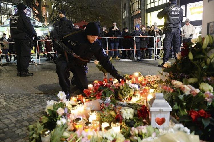 AL996 BERLÍN (ALEMANIA), 20/12/2016.- Un policía deposita unas flores en memoria de las víctimas en el lugar del atentado en Berlín, Alemania, hoy 20 de diciembre de 2016. Al menos doce personas murieron este lunes y unas cincuenta resultaron heridas al ser arrolladas por un camión que irrumpió en un mercadillo navideño del centro de Berlín, objetivo presuntamente de un atentado. EFE/Maurizio Gambarini