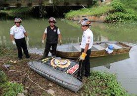 Bomberos rodean el cadáver de Norman Alejandro Ichich, quien fue localizado en el río Cahabón, en Cobán. (Foto Prensa Libre: Eduardo Sam).
