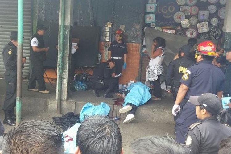 Locatarios observan los cadáveres, mientras socorristas los cubren. (Foto Prensa Libre: Cortesía)