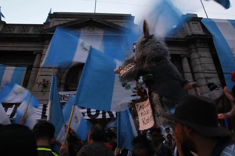 Manifestantes usan piñatas para mostrar su descontento contra los diputados. (Foto Prensa Libre: Paulo Raquec).