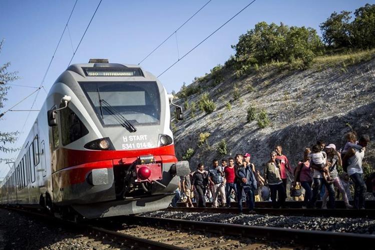 Migrantes caminan al costado de la vía férrea ante la negativa de ser transportados en los trenes. (Foto Prensa Libre: EFE).
