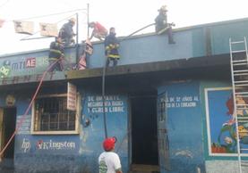 Socorristas extinguen el fuego en los locales comerciales de Cuyotenango. (Foto Prensa Libre: Cristian Icó)