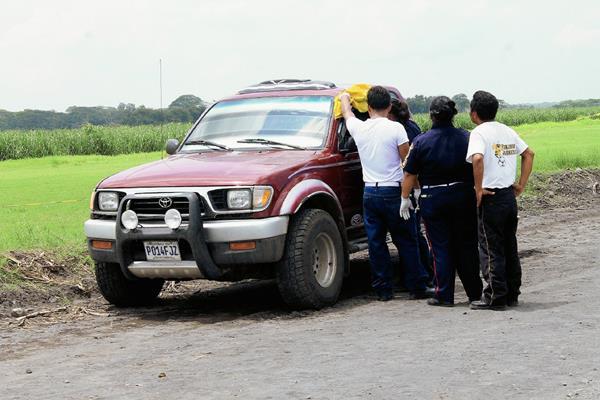 Socorristas examinan el cuerpo de Edin Morales, quien fue atacado a balazos en Masagua, Escuintla y murió. (Foto Prensa Libre: Carlos E. Paredes)