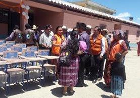 La candidata Ajín Tecún y los que la acompañan llegan con chalecos color naranja a hacer la entrega de pupitres en la escuela de la aldea Patachaj, de San Cristóbal Totonicapán. (Foto Prensa Libre: Lucero Sapalú)