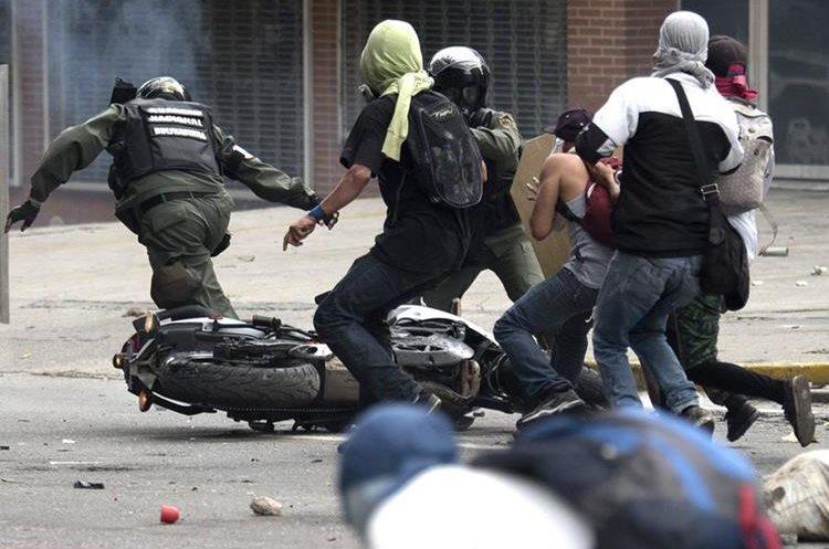 Un grupo de manifestantes logra frenar el paso de dos agentes de la Guardia Nacional.