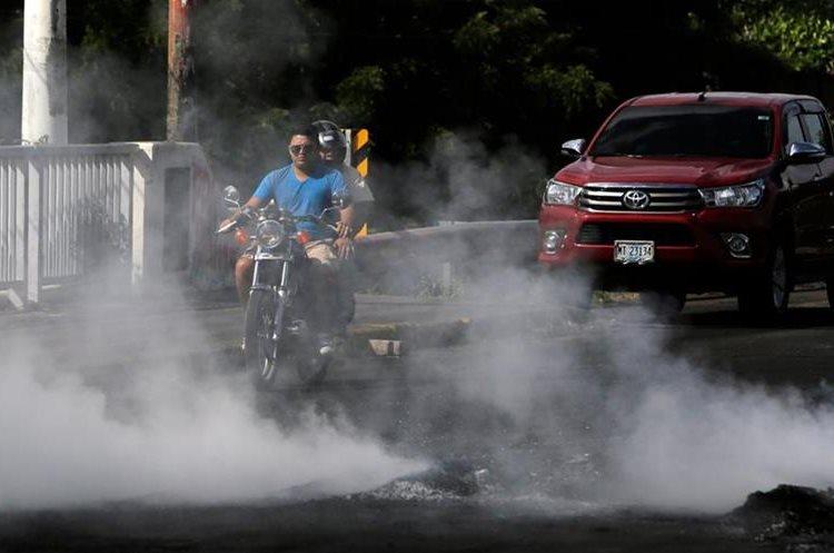 Un motociclista se ve bloqueado por el humo de la quema de neumáticos, en la ciudad de Sebaco, a unos 100 km de Managua. (AFP).