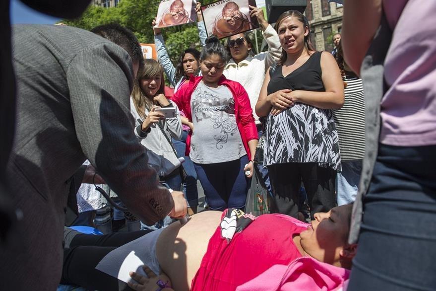 Una mujer que rechaza el aborto permite que un doctor amplifique el sonido del corazón de su bebé durante una protesta. (Foto Prensa Libre: AP).