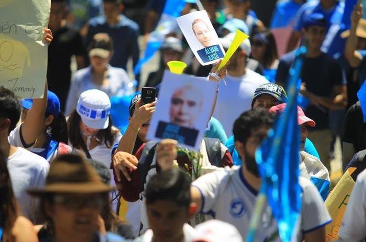 Varios rostros de los diputados son repartidos entre los manifestantes.