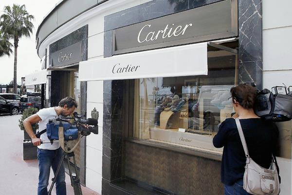 Periodistas trabajan en frente de la tienda de joyas de Cartier en la Croisette en Cannes, Costa Azul, donde se cometió el atraco. (Foto Prensa Libre: AFP).
