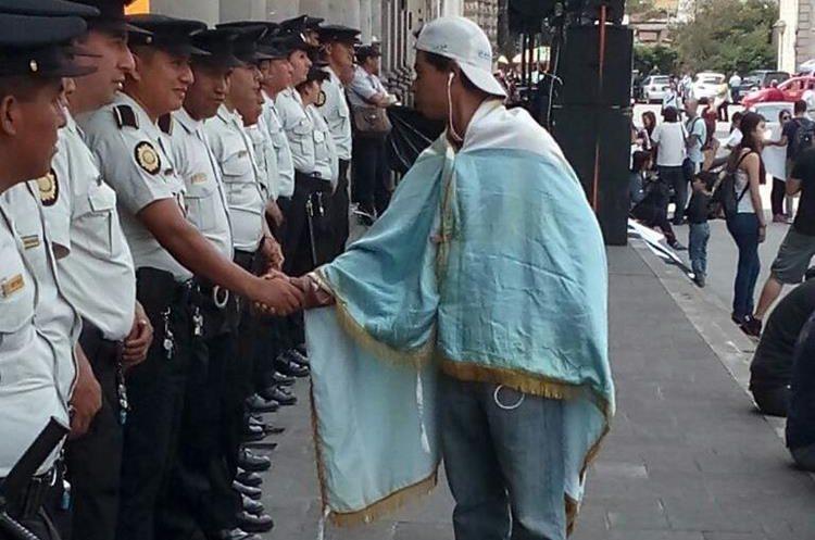 Un manifestante saluda y felicita a los agentes por su extenuante labor.