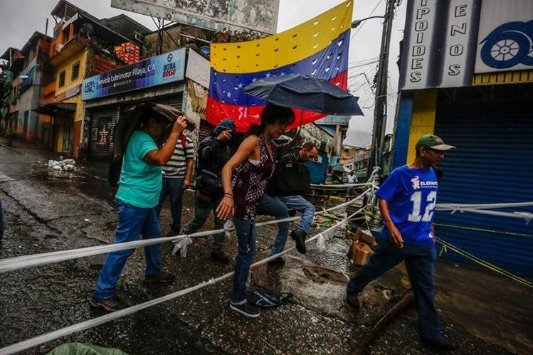Transeúntes cruzan una calle bloqueada por manifestantes opositores en Caracas.(EFE).