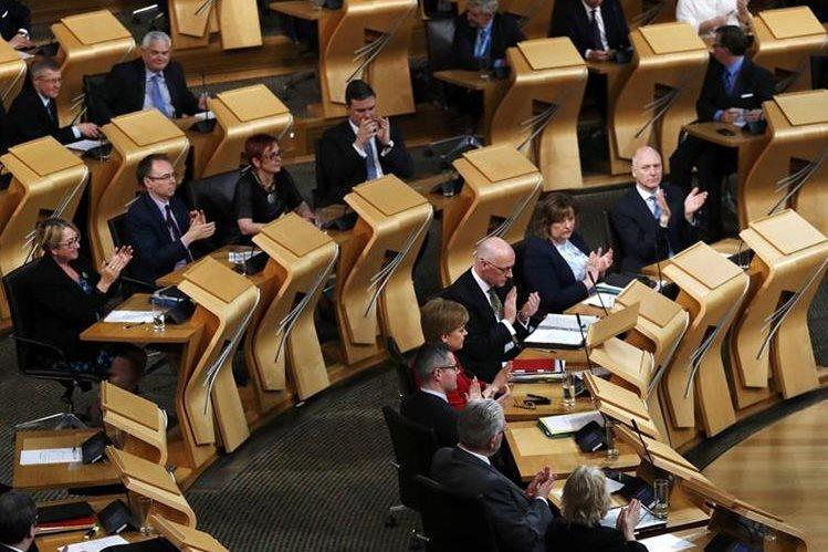Diputados aplauden tras la votación que avaló el primer paso de secesión de Escocia. (Foto Prensa Libre: AFP)