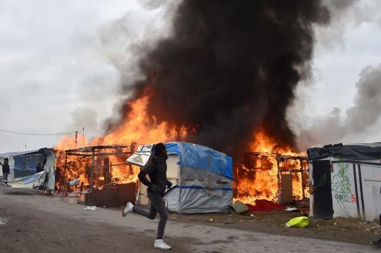 Un refugiado corre frente a las precarias viviendas en llamas en el campamento de migrantes de Calais. (Foto Prensa Libre: AFP).