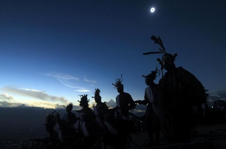 TOPSHOT - Dancers perform as a solar total eclipse occurs in Matantimali, Central Sulawesi on March 9, 2016.   A total solar eclipse swept across the vast Indonesian archipelago, witnessed by tens of thousands of sky gazers and marked by parties, Muslim prayers and tribal rituals. / AFP / STRINGER