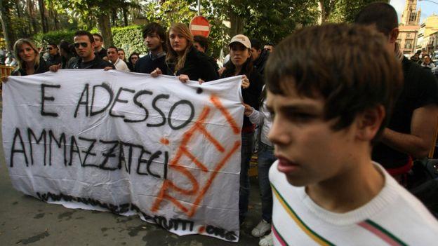 """""""Y ahora mátenos a todos nosotros"""", dice la bandera que llevan activistas anti-mafia en una protesta en 2007, en Palermo, Italia. GETTY/MARCELLO PATERNOSTRO"""
