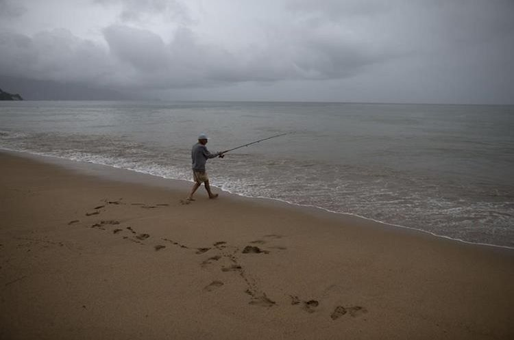 Mike Anderson of Minnesota fishes in the Pacific Ocean during a steady rain as Hurricane Patricia approaches Puerto Vallarta, Mexico, Friday, Oct. 23, 2015. Hurricane Patricia barreled toward southwestern Mexico Friday as a monster Category 5 storm, the strongest ever in the Western Hemisphere.  (AP Photo/Rebecca Blackwell)