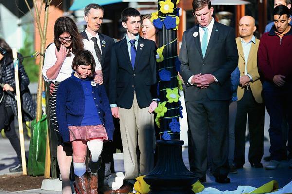 La familia del niño fallecido en los atentados de Boston, participan en una ceremonia conmemorativa junto con autoridades. (Foto Prensa Libre: AP).
