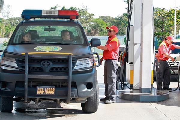agentes de la Policía abastecen de combustible un vehículo de esa institución en el bulevar El Naranjo, Mixco. Se informó que solo reciben tres galones diarios.