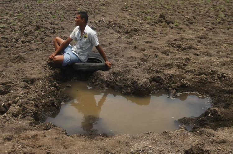 Wilman Estrada, vecino de Atescatempa, Jutiapa, lamenta que la laguna  se haya secado, pues en ella pescaba para ganarse la vida. (Foto Prensa Libre: AFP)
