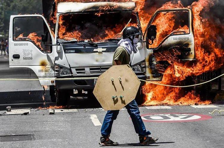 Un camión fue encendido por opositores que bloquea una avenida en Caracas. (AFP).