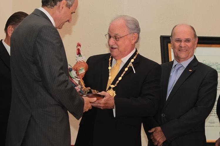 Ricardo Castillo Sinibaldi (al centro) recibe, de manos de Raúl Castillo Zaghi, una figura de gallo que incluye la Orden de Cervecería Centroamericana. A la derecha, Juan Monge Calderón. (Foto Prensa Libre: Edwin Castro)