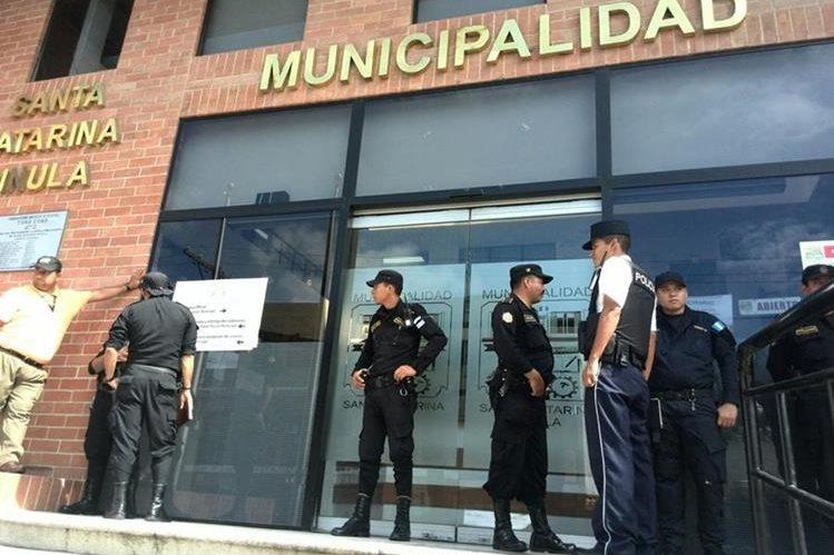 Miembros de la Policía Nacional Civil resguardan el ingreso a la Municipalidad de Santa Catarina Pinula donde se efectúan allanamientos. (Foto Prensa Libre: Estuardo Paredes)