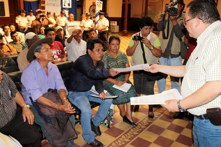 El secretario municipal, Otto Lang, entrega copia del acuerdo a pobladores que abogan por la nacionalización del servicio eléctrico. (Foto Prensa Libre: Óscar Figueroa)