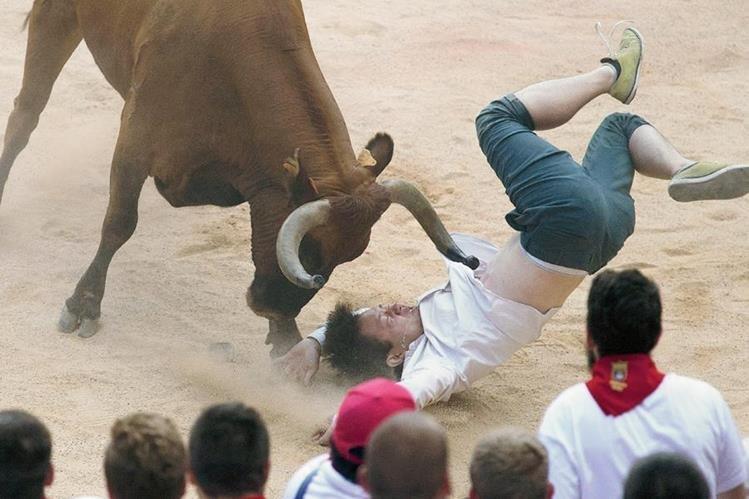 Un corredor es embestido por un toro durante el segundo encierro de los sanfermines, en Pamplona, España. (Foto Prensa Libre:EFE)