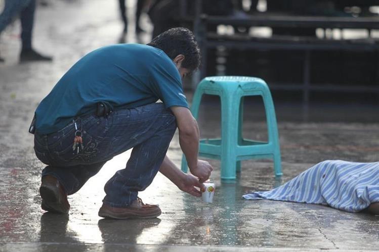 Un locatario del mercado de Jocotales, en la zona 6, coloca una veladora junto al cuerpo de la joven víctima.(Foto Prensa Libre: Érick Ávila)