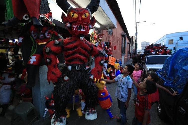 Un grupo de niños elige la piñata que quemarán en las ventas del parque Colón