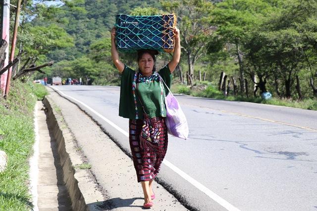 Mujer camina debido al bloqueo en la ruta que se dirige al área fronteriza con México, La Democracia. (Foto Prensa Libre: Mike Castillo)