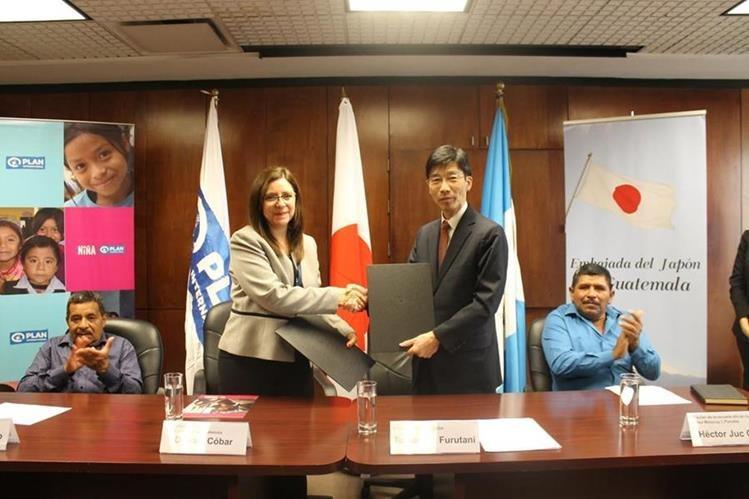 Débora Cóbar, directora de Plan Internacional, y Tomohiko Furutani, embajador del Japón, -al centro- luego de la firma del convenio de cooperación. (Foto Prensa Libre: Cortesía).