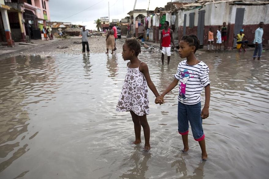 Girls hold hands as they help each other wade through a flooded street after the passing of Hurricane Matthew in Les Cayes, Haiti, Thursday, Oct. 6, 2016. Two days after the storm rampaged across the country