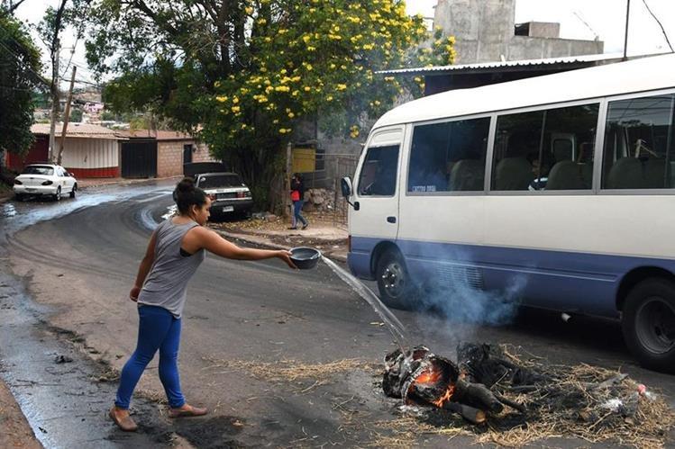 Una mujer intenta extinguir el fuego de una barricada establecida durante las protestas en Tegucigalpa, Honduras. (Foto Prensa Libre: AFP)