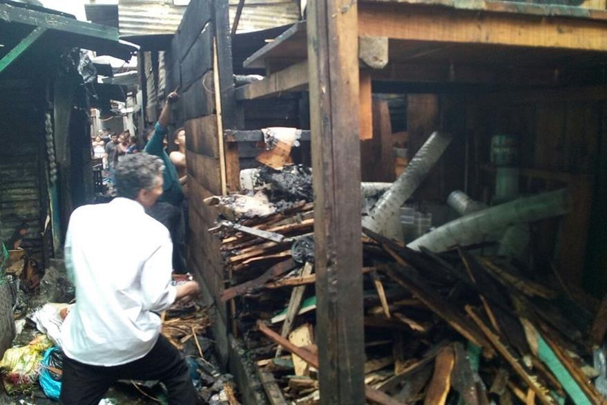 Comerciantes intentan recuperar algunas pertenencias después de que los socorristas apagaron el incendio. (Foto Prensa Libre: Érick Ávila)